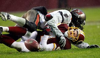 Washington Redskins place kicker Graham Gano, bottom, is tackled by Tampa Bay Buccaneers cornerback E.J. Biggers after Gano's extra point kick is botched during the second half of an NFL football game in Landover, Md., Sunday, Dec. 12, 2010. Tampa Bay won 17-16. (AP Photo/Evan Vucci)
