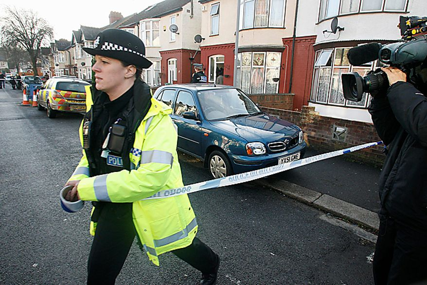 """A police officer cordons off the area before a car, center,  is removed from outside the house which was searched by British police in Luton, England, Monday, Dec. 13, 2010. A Swedish prosecutor says police are """"98 percent"""" certain the Stockholm suicide bomber is 28-year-old Taimour Abdulwahab who is a Swedish citizen but also lived several years in Britain. Prosecutor Tomas Lindstrand Monday said Abdulwahab has his roots in the Middle East and has been a Swedish citizen since 1992. Lindstrand said Abdulwahab was also the registered owner of the car that exploded in Stockholm shortly before the suicide blast Saturday. (AP Photo/Akira Suemori)"""