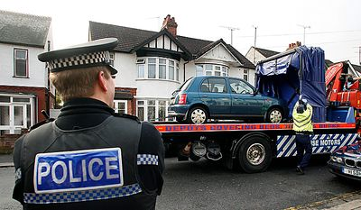 """A police officer looks on as a car is removed from outside the house which was searched by British police in Luton, England, Monday, Dec. 13, 2010. A Swedish prosecutor says police are """"98 percent"""" certain the Stockholm suicide bomber is 28-year-old Taimour Abdulwahab who is a Swedish citizen but also lived several years in Britain. Prosecutor Tomas Lindstrand Monday said Abdulwahab has his roots in the Middle East and has been a Swedish citizen since 1992. Lindstrand said Abdulwahab was also the registered owner of the car that exploded in Stockholm shortly before the suicide blast Saturday. (AP Photo/Akira Suemori)"""