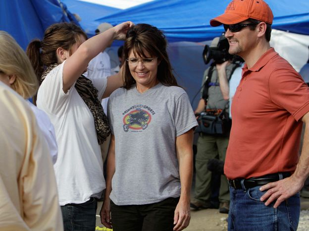 "Sarah Palin's daughter Bristol adjusts her mother's hair at a cholera treatment center in Haiti. Caption writers said Mrs. Palin was getting ""her hair done."" (Associated Press)"