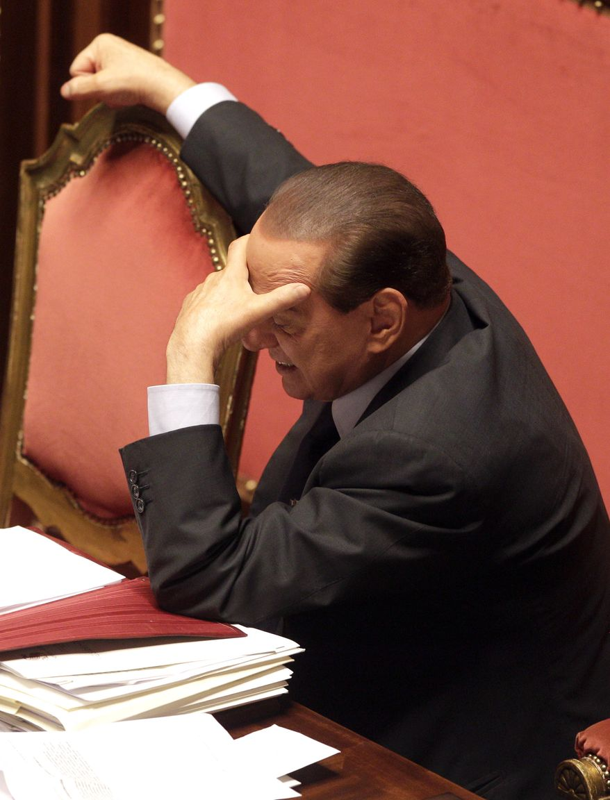 Italian Prime Minister Silvio Berlusconi holds his head during a session at the Senate, in Rome, Monday, Dec. 13, 2010. Mr. Berlusconi won confidence votes in chambers of parliament Tuesday. (AP Photo/Pier Paolo Cito)