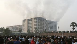 A crowd gathers as smoke rises from a garment factory at Ashulia, Bangladesh, about 16 miles north of the capital of Dhaka, on Tuesday, Dec. 14, 2010. A devastating blaze raced through the factory, killing at least 25 people and injuring more than 100, witnesses and news reports said. (AP Photo/Pavel Rahman)
