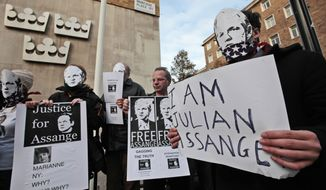 Supporters of WikiLeaks founder Julian Assange, some holding placards and wearing masks depicting him, demonstrate outside the Swedish Embassy in central London on Monday, Dec. 13, 2010. (AP Photo/Lefteris Pitarakis)