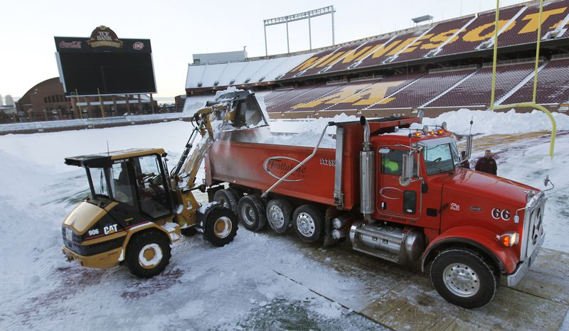 A front-end loader dumps snow in to a truck as workers remove snow from the field of TCF Stadium, home of the University of Minnesota's football team, Tuesday, Dec. 14, 2010, in Minneapolis. The Minnesota Vikings said Tuesday they're getting ready to use the stadium as a backup if the torn Metrodome roof can't be repaired before Monday night's game against the Chicago Bears. (AP Photo/The Star Tribune, Richard Tsong-Taatarii)