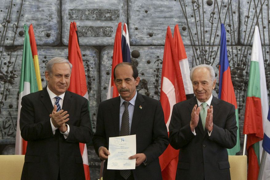 Israeli Prime Minister Benjamin Netanyahu, left, and Israeli President Shimon Peres, right, stand with a representative of the Palestinian Authority, name not known, as he accepts a certificate of appreciation and award for Palestinian help in fighting the wildfires at the Carmel forest in northern Israel, during a ceremony in Jerusalem, Tuesday, Dec. 7, 2010. Another ceremony to honor the Palestinian firefighters was canceled Tuesday, Dec. 14, 2010, when most of the Palestinians did not get their permits to enter Israel. (AP Photo/Tara Todras-Whitehill)