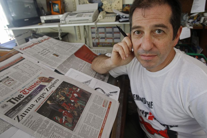 Cartoonist Jonathan Shapiro, who signs his work as 'Zapiro', poses for a photo next to a local newspaper at his office in Cape Town, South Africa, Tuesday, Dec. 14, 2010. South Africa's president has filed a $700,000 defamation suit over a cartoon depicting him with his pants undone, preparing to rape a blindfolded, female figure symbolizing justice, a lawyer said Tuesday. (AP Photo/Schalk van Zuydam)