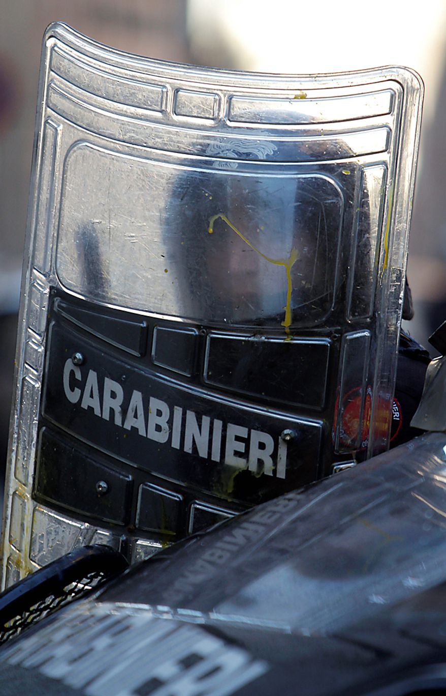 A Carabinieri officer is seen behind a shield during clashes in Rome, Tuesday, Dec. 14, 2010. Prime Minister Silvio Berlusconi won back-to-back votes of confidence in the Italian parliament Tuesday, but he was left with a razor-thin majority that will make it hard for him to govern effectively. In the second and most dramatic of the tests, Mr. Berlusconi survived a no-confidence motion in the lower house by just three votes. The tense session was briefly interrupted as lawmakers pushed and shoved each other, while outside parliament protesters hurling firecrackers, eggs and paint scuffled with police. (AP Photo/Pier Paolo Cito)