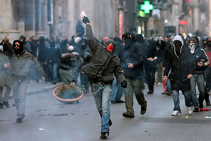 Demonstrators clash with police in Rome, Tuesday, Dec. 14, 2010. Outside parliament, thousands of students, some of them downing beers as they marched, smashed shop windows, destroyed bank ATMs and set at least three vehicles on fire. At one point they even entered a bank, prompting staffers to try to barricade themselves inside. Police fired tear gas as the protesters neared Prime Minister Silvio Berlusconi's residence. Mr. Berlusconi won back-to-back votes of confidence in the Italian parliament Tuesday to survive one of the toughest tests of his political life. But he was left with a razor-thin majority that will make it hard for him to govern effectively. (AP Photo/Gregorio Borgia)