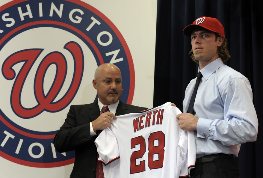 The Washington Nationals newest outfielder Jason Werth holds his new baseball jersey as he stands with Nationals General Manager Mike Rizzo during a news conference at Nationals Park in Washington, Wednesday, Dec. 15, 2010. (AP Photo/Susan Walsh)