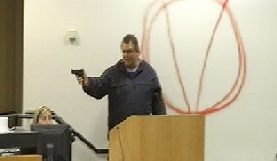 In this image taken from video and released by WJHG-TV, Clay A. Duke points a handgun at Bay City school board members and staff on Tuesday, Dec. 14, 2010, in Panama City, Fla. (AP Photo/WJHG-TV)