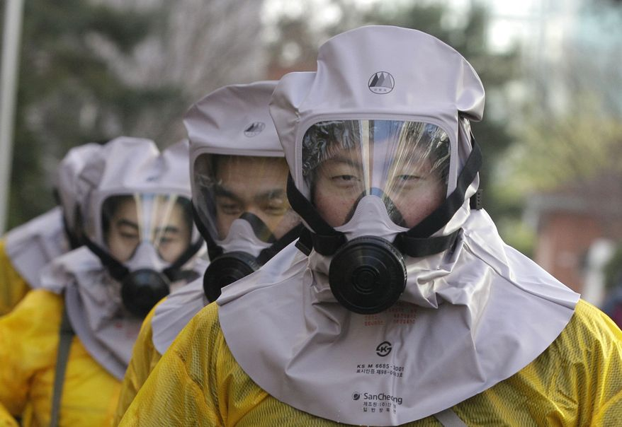 South Koreans wear gas masks during a civil defense drill simulating a North Korean attack near the border city of Paju, South Korea, on Wednesday, Dec. 15, 2010. (AP Photo/Lee Jin-man)