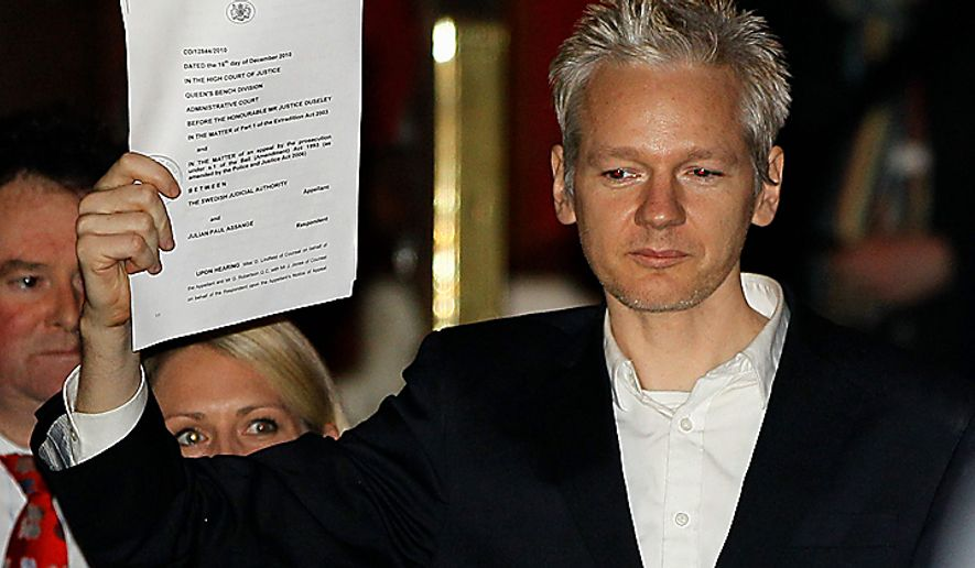 WikiLeaks founder Julian Assange holds up a court document for the media after he was released on bail, outside the High Court in London, Thursday, Dec. 16, 2010. Mr. Assange has been released on bail following a week of legal drama over his extradition. (AP Photo/Kirsty Wigglesworth)