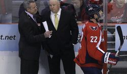 **FILE** Washington Capitals assistant coach Dean Evason (left) talks with Washington Capitals head coach Bruce Boudreau during the first period of the Capitals' 2-1 loss to the Anaheim Ducks at the Verizon Center in Washington on Dec. 15, 2010. (Associated Press)