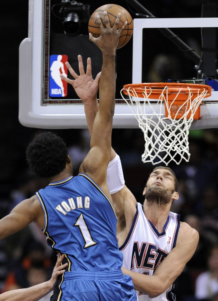 Washington Wizards' Nick Young (1) is fouled by New Jersey Nets' Brook Lopez during the first quarter of an NBA basketball game Thursday, Dec. 16, 2010, in Newark, N.J. (AP Photo/Bill Kostroun)