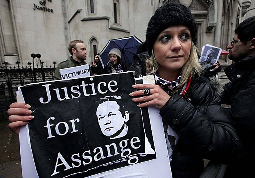 A protester holds a banner in support of WikiLeaks founder Julian Assange outside the High Court in London where a judge dismissed Sweden's appeal against bail for Mr. Assange.  (AP Photo/Matt Dunham)