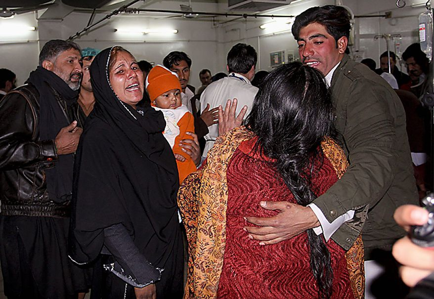 Family members of an injured person weep at a local hospital in Peshawar, Pakistan, Thursday, Dec. 16, 2010, after an assailant threw an explosive device at Shi'ite Muslims in a Muharram procession in the city, wounding several people, two of them critically, police said. (AP Photo/Mohammad Sajjad)