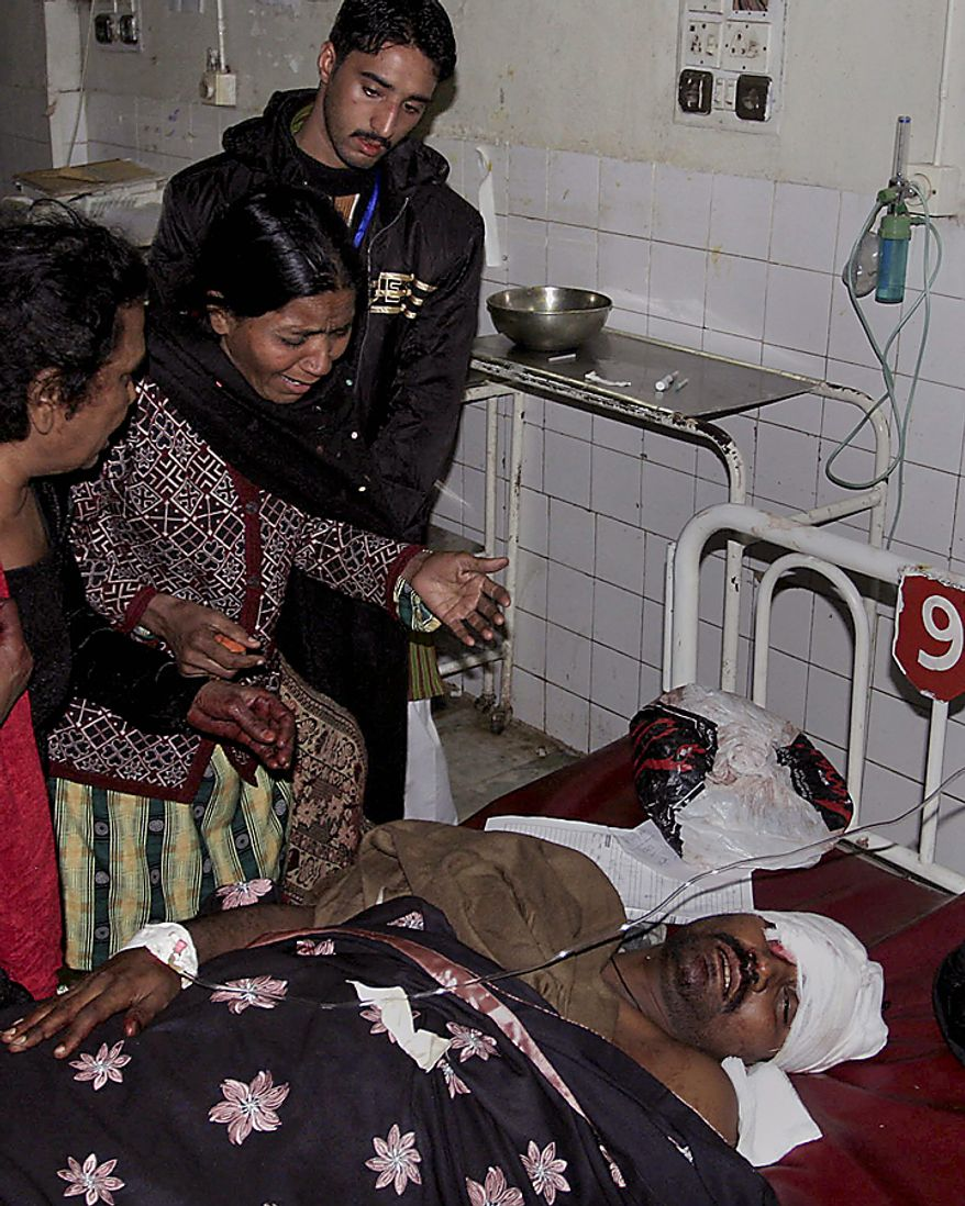 A woman weeps while visiting an injured family member at a local hospital in Peshawar, Pakistan, on Thursday, Dec. 16, 2010, after an assailant threw an explosive device at Shi'ite Muslims in a Muharram procession in in the city, wounding several people. (AP Photo/Mohammad Sajjad)