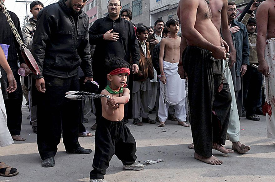 A Shi'ite Muslim child beats himself with bladed chains during a Muharram procession in Peshawar, Pakistan, on Thursday, Dec. 16, 2010. Muharram is observed around the world for ten days as mourning in remembrance of the martyrdom of Imam Hussein, the grandson of Prophet Muhammad. (AP Photo/Mohammad Sajjad)