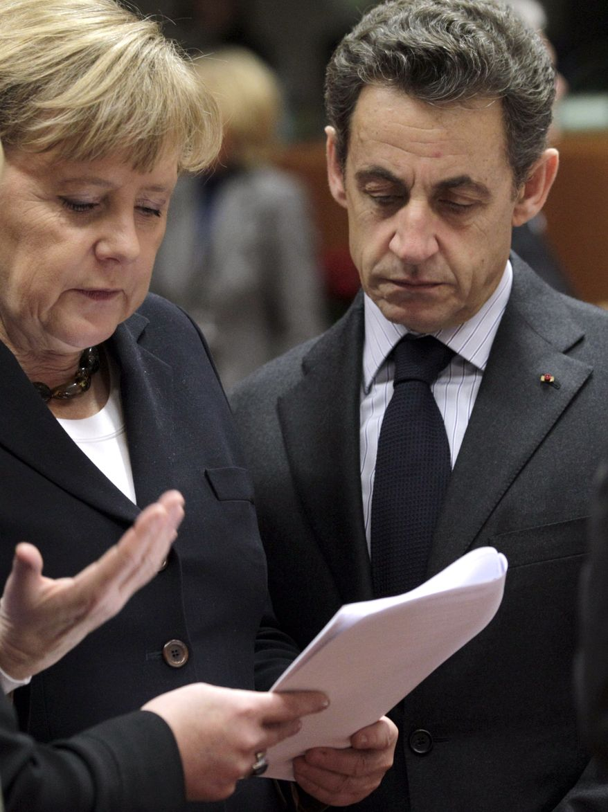 German Chancellor Angela Merkel, left, looks over papers with French President Nicolas Sarkozy during a round table meeting at an EU summit in Brussels, Friday, Dec. 17, 2010. (AP Photo/Yves Logghe)