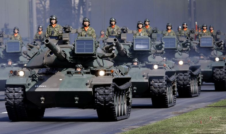 In this Oct. 28, 2007, file photo, Japan Ground Self-Defense Force tanks rumble during a military parade, marking the 57th anniversary of the founding of the Japan Self-Defense Forces at Asaka Base, north of Tokyo. Japan should refocus its defense strategy on the rise of China and not on the Cold War threat of Russia, according to new guidelines announced Friday Dec. 17, 2010. (AP Photo/Itsuo Inouye, File)