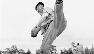 """FILE- In this Feb. 28, 1941, file photo, Cleveland Indians star pitcher Bob Feller works on his form during spring training baseball in Fort Myers, Fla. Feller, the Iowa farm boy whose powerful right arm earned him the nickname """"Rapid Robert"""" and made him one of baseball's greatest pitchers during a Hall of Fame career with the Indians, has died Wednesday, Dec. 15, 2010. He was 92.  (AP Photo/File)"""