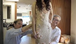 This undated photo courtesy of Badgley Mischka shows Mark Badgley, right, and James Mischka, left, as they style Rumer Willis on the set of their spring 2011 marketing campaign. Fashion house Badgley Mischka has chosen Willis as its newest spokesmodel.     (AP Photo/Badgley Mischka) NO SALES