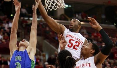 Ohio State's Dallas Lauderdale (52) taps the ball in for two between Florida-Gulf Coast's Chase Fieler (20), Anthony Banks (32) and Ohio State's Jared Sullinger (0) during the first half of an NCAA college basketball game Wednesday, Dec. 15, 2010, in Columbus, Ohio. (AP Photo/Terry Gilliam)