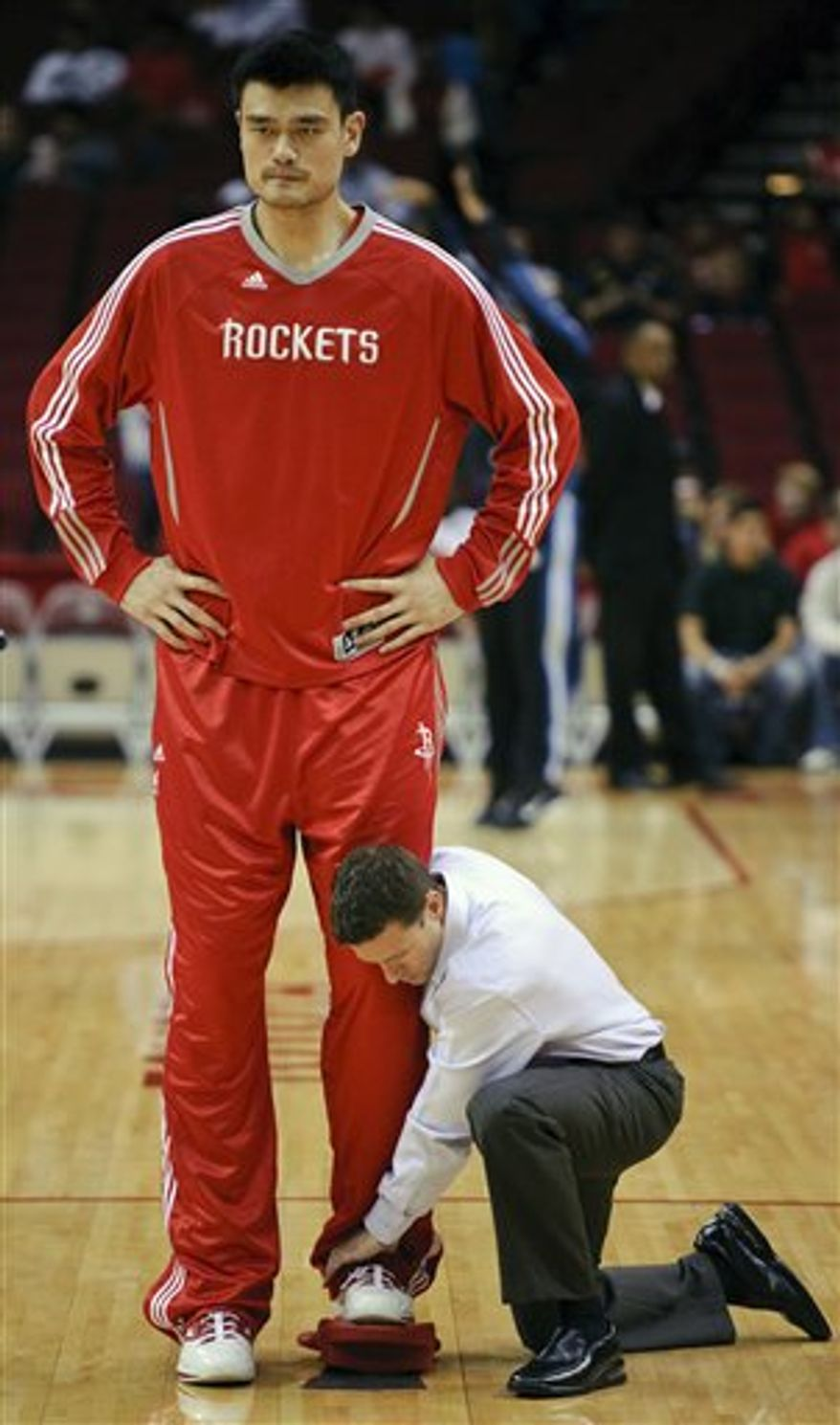 FILE - In this file photo taken Nov. 7, 2010, Houston Rockets trainer Jason Biles, left, works on the left foot of center Yao Ming, of China, before the Rockets' NBA basketball game against the Minnesota Timberwolves in Houston. Ming, 30, will miss the rest of the season because of a stress fracture in his left ankle. The Rockets announced the decision Friday, Dec. 17, 2010, a day after the injury was found in an MRI exam. Team physician Walter Lowe said surgery is the usual treatment for such an injury, which has sidelined Yao since Nov. 10. (AP Photo/Dave Einsel, File)