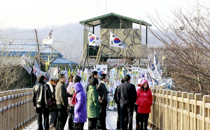 South Korean national flags fly near the barbed wire fence decorated with messages wishing for reunification of the two Koreas as tourists look at the north side at the Imjingak Pavilion near the border village of Panmunjom, the demilitarized zone (DMZ), in Paju, South Korea, Saturday, Dec. 18, 2010. South Korea said Saturday it will go ahead with artillery drills on a border island shelled by North Korea last month despite Pyongyang's threat to retaliate again, as Russia and China expressed concerns over tension on the volatile peninsula. (AP Photo/Lee Jin-man)