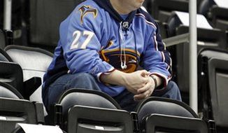 An Atlanta Thrashers fan sits alone among empty seats during an NHL hockey game on Thursday, Dec. 16 2010, in Atlanta. The Thrashers are on pace to earn only the second playoff spot in franchise history, but the team ranks 28th in the NHL in average attendance, prompting concern by the NHL.  (AP Photo/John Bazemore)