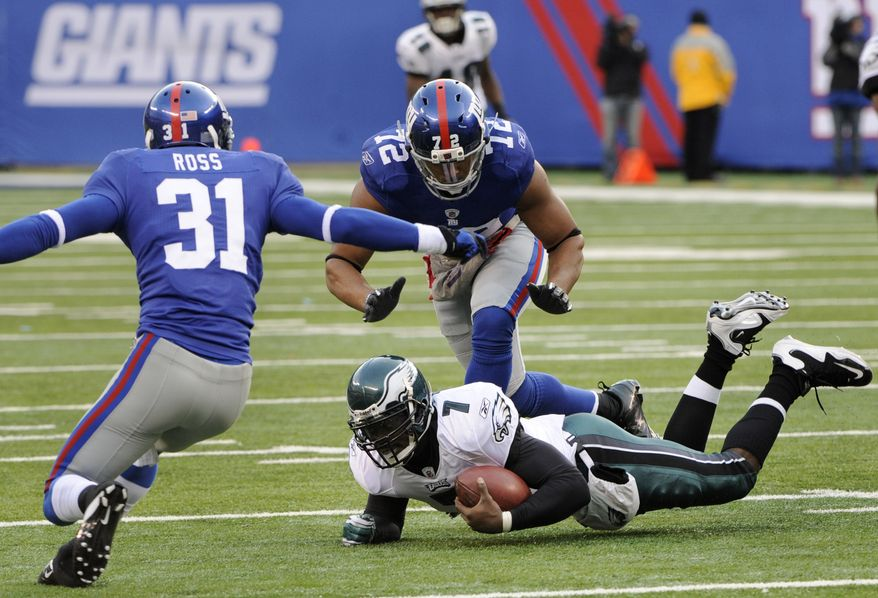 Philadelphia Eagles quarterback Michael Vick falls on the ground while being persued New York Giants' Aaron Ross, left, and Osi Umenyiora during the second quarter of an NFL football game at New Meadowlands Stadium, Sunday, Dec. 19, 2010, in East Rutherford, N.J. (AP Photo/Bill Kostroun)