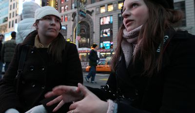 "Victoria Melnikow (left) looks on as her sister Cassandra Melnikow is interviewed about news of the Senate's repeal of ""don't ask, don't tell"" on Saturday, Dec. 18, 2010, in New York's Times Square. (AP Photo/Tina Fineberg)"