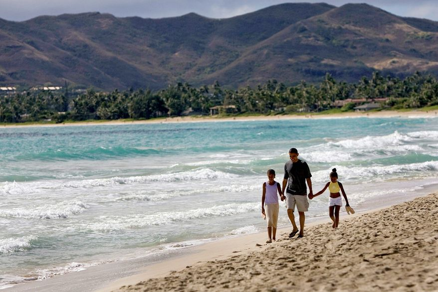 Then-Sen. Barack Obama walks the beach with daughters Malia (left) and Sasha during a vacation in Kailua, Hawaii, Aug. 12, 2008. The community is full of excitement over the family's return. (Associated Press)