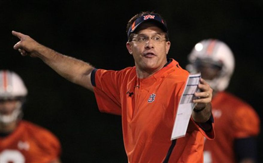 "FILE - This is an Aug. 2, 2010 file photo shows Auburn offensive coordinator Gus Malzahn directing his players on the opening day of practice in Auburn, Ala.  Malzahn says he is waiting for the ""right time, right place"" to become a head coach. Vanderbilt apparently wasn't that place. Malzahn would not talk about the Vanderbilt head coaching position in an interview Wednesday, Dec. 15, 2010 but said that he does want to run his own program ""somewhere down the line."" (AP Photo/Dave Martin, File)"