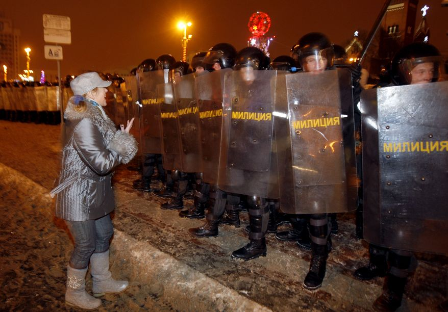 An opposition supporter appeals to riot policemen during a rally in Minsk, Belarus, late Sunday, Dec. 19, 2010. Thousands of opposition supporters in Minsk, the capital, tried to storm the main government building to protest what the opposition claims was large-scale vote-rigging in Sunday's presidential election. (AP Photo/Sergei Grits)