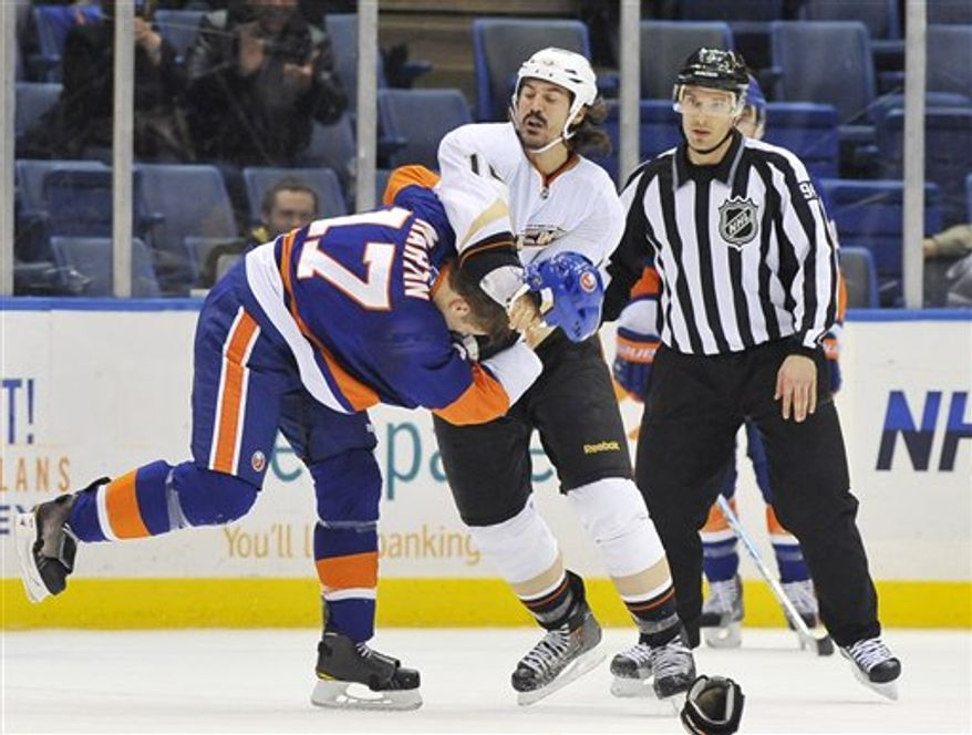 **FILE** Anaheim Ducks right wing George Parros (16) and New York Islanders left wing Matt Martin fight during the second period of the Islanders' 3-2 win in Uniondale, N.Y., on Dec. 16, 2010. (Associated Press)