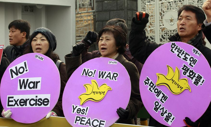 South Korean protesters shout slogans during a rally denouncing the South Korea's live-fire drills on Yeonpyeong Island, in front of Defense Ministry in Seoul Monday, Dec. 20, 2010. (AP Photo/ Lee Jin-man)