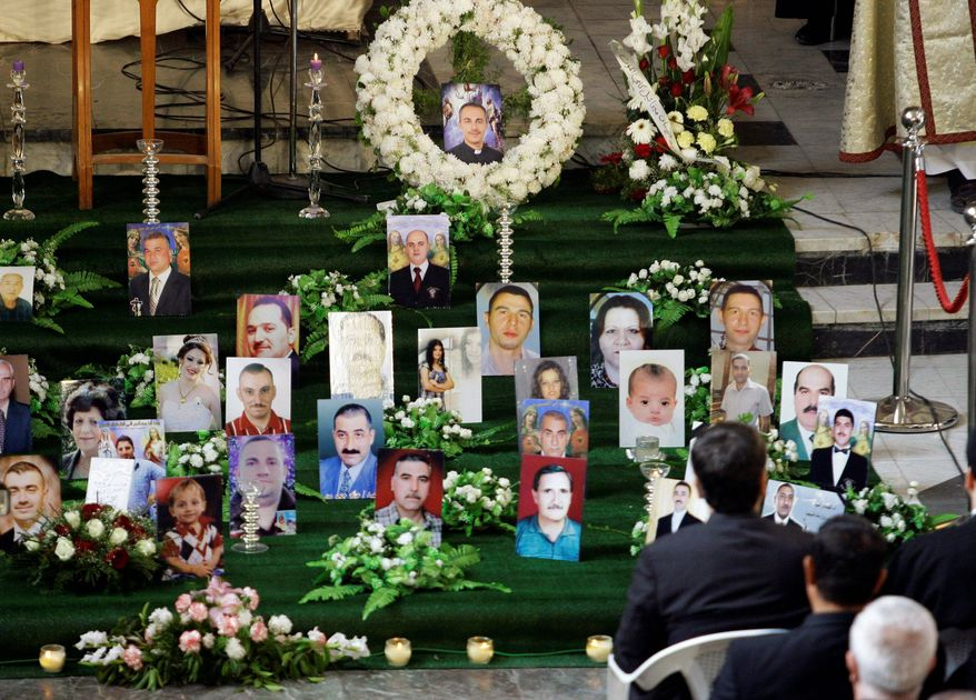 Pictures of slain Iraqi Christians are displayed during Mass Dec. 10 at Our Lady of Salvation church in Baghdad. Sixty-eight persons died in a bombing there on Oct. 31, and days later, a string of bombs went off outside Christian homes in the city. (Associated Press)