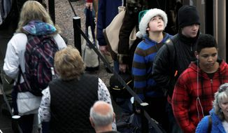 Colter Schoer, 10, of Denver shows some Christmas spirit with a Santa hat as he waits in a long line for a security check. (Associated Press)