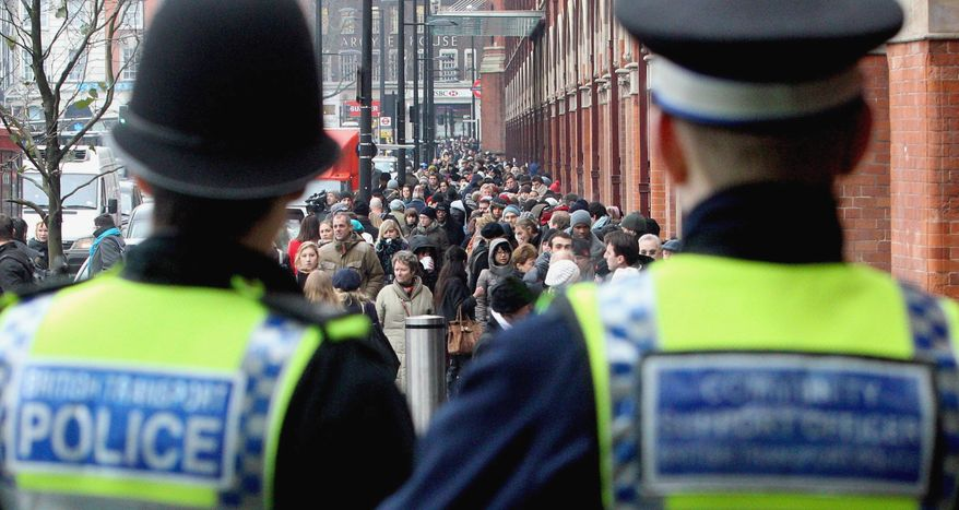 Police look on as hundreds of people queue outside St. Pancras Station in London for the Eurostar train to France and Belgium on Tuesday, Dec. 21, 2010. (AP Photo/Lewis Whyld, PA Wire)