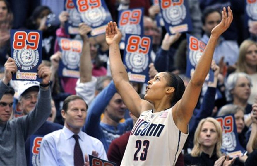 Connecticut forward Maya Moore (23) drives for a layup in front of Florida State forward Natasha Howard (33) in the first half of an NCAA basketball game in Hartford, Conn., Tuesday, Dec. 21, 2010. Heading into the game, Connecticut needed one win to set the NCAA record for consecutive wins. (AP Photo/Jessica Hill)