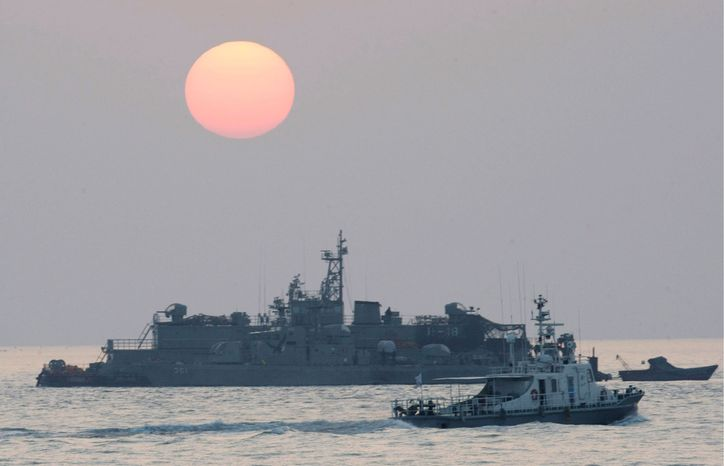 ASSOCIATED PRESS PHOTOGRAPHS A government ship sails past the South Korean Navy's floating base at sunrise Wednesday near Yeonpyeong island, South Korea.