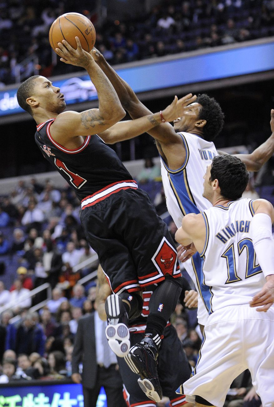 Chicago Bulls guard Derrick Rose, left, goes to the basket against Washington Wizards shooting guard Nick Young, center, and Kirk Hinrich, lower right, during the first half of an NBA basketball game, Wednesday, Dec. 22, 2010, in Washington. (AP Photo/Nick Wass)