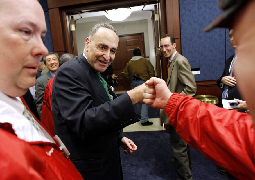 Sen. Charles Schumer, D-N.Y., left, fist bumps John Feal after a news conference, on Capitol Hill in Washington, Wednesday, Dec. 22, 2010, after Senate passage of a bill to assist 9/11 First Responders. (AP Photo/Alex Brandon)