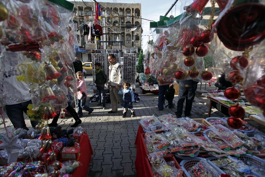 People walk past a street vendor selling Christmas decorations in downtown Baghdad, Iraq, on Wednesday, Dec. 22, 2010. Church officials in Iraq say they have canceled some Christmas festivities in two northern cities over fears of insurgent attacks. (AP Photo/Hadi Mizban)