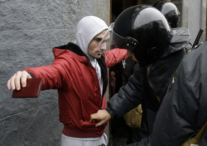 ** FILE ** Riot police officers search a man at a square outside the Kievsky train station, amid fears of a repeat of Saturday's clashes, in Moscow on Wednesday, Dec. 15, 2010. (AP Photo/Mikhail Metzel)