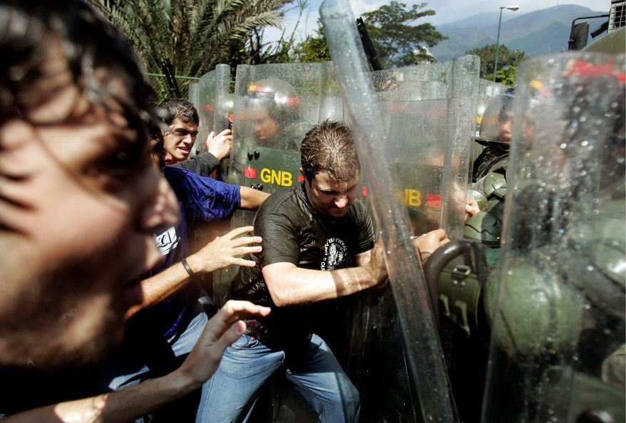 Associated Press photographs Demonstrators clash with soldiers Thursday outside the Central University of Venezuela in Caracas. Students protested against a law that increases government powers over the country's universities.
