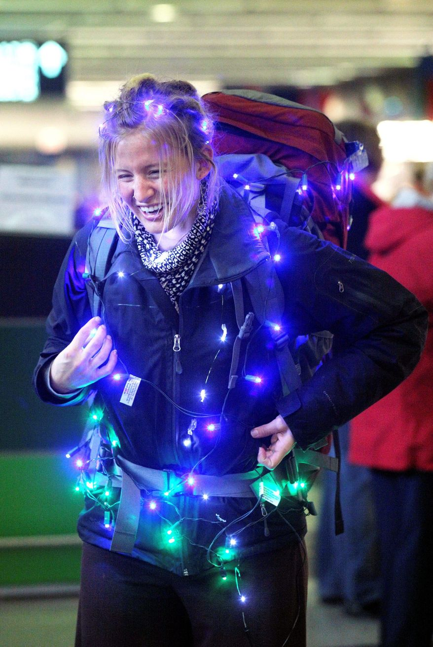 BLOOMBERG Cali Simpson wraps herself in holiday lights Thursday upon arriving at Chicago's O'Hare airport from Denver. Travelers generally were faring well.