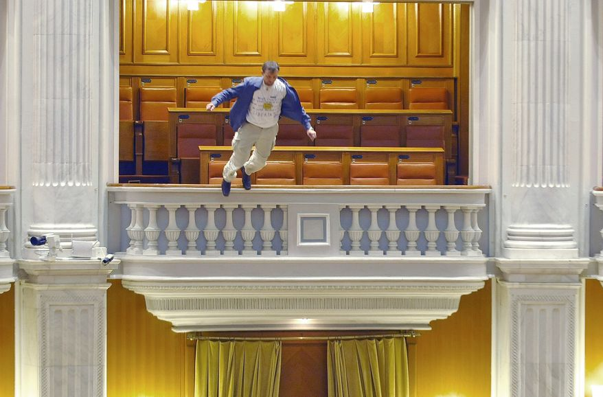 Adrian Sobaru, an electrician with the national television network, throws himself from a balcony in Romania's Parliament on Thursday, Dec. 23, 2010, just as the prime minister began to speak ahead of a no-confidence vote. (AP Photo/Bogdan Stamatin, Mediafax Foto)