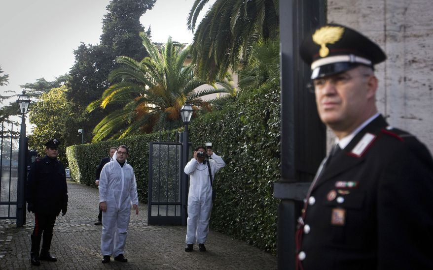 Forensic officers of the Carabinieri inspect the area inside the Swiss Embassy compound in Rome, where a package exploded on Thursday, Dec. 23, 2010. (AP Photo/Angelo Carconi)